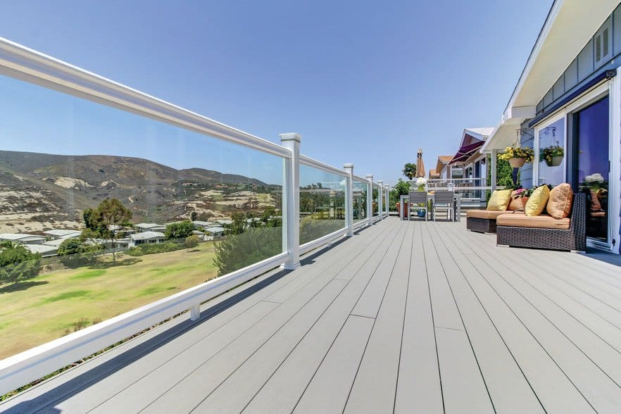 Deck featuring TimberTech PRO Terrain Collection in Stone Ash RadianceRail white glass with outdoor furniture