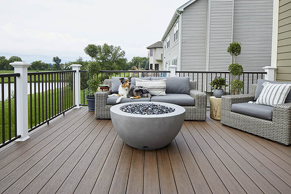 Black composite decking TimberTech PRO Reserve Collection in Dark Roast with dog laying on furniture