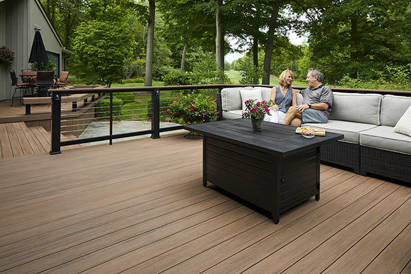 Decking boards featuring TimberTech AZEK Vintage Collection in English Walnut with Couple sitting on outdoor furniture