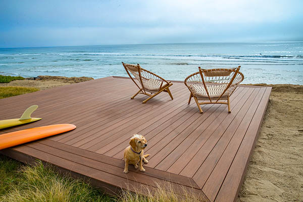 Picture frame composite deck featuring TimberTech AZEK Vintage Collection in Mahogany on the beach with dog