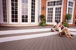 Deck featuring TimberTech AZEK Harvest Collection in Kona with couple sitting on steps