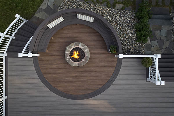 Aerial view of a curved deck built from TimberTech AZEK Vintage Collection decking in Coastline, Mahogany, and Dark Hickory