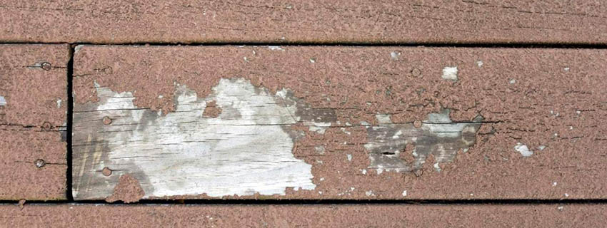 Wood deck stain that has cracked and faded.