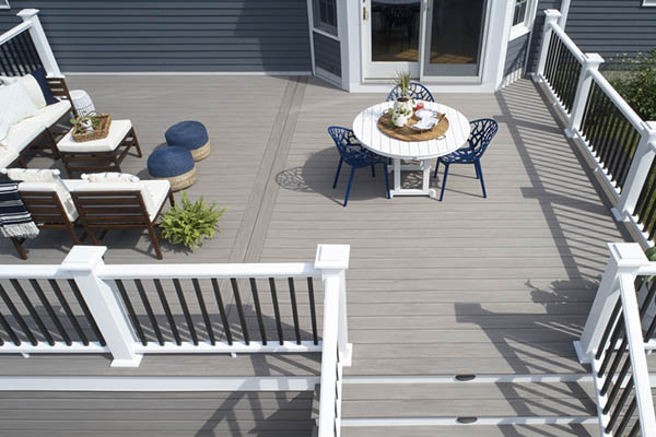 A sunny composite deck with two sections for lounging and dining